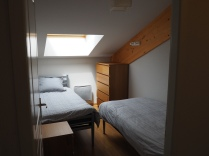 Twin bedroom with x2 single beds, x1 bedside drawers, x2 bedside lamps, x1 large chest of drawers & wall hooks
